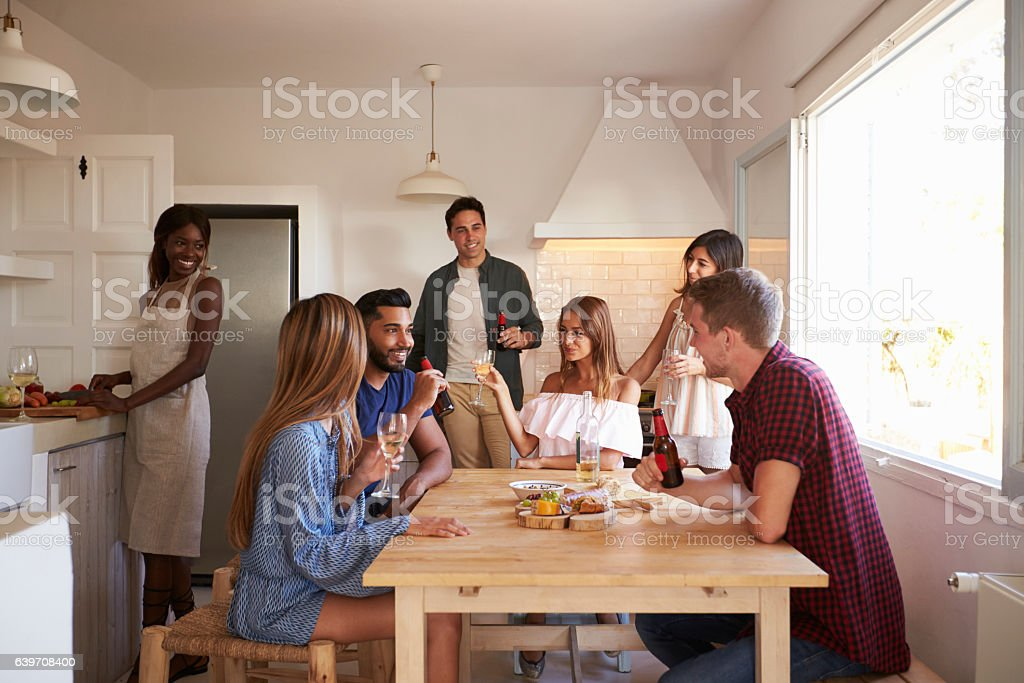 Group of friends talk in kitchen, one preparing food