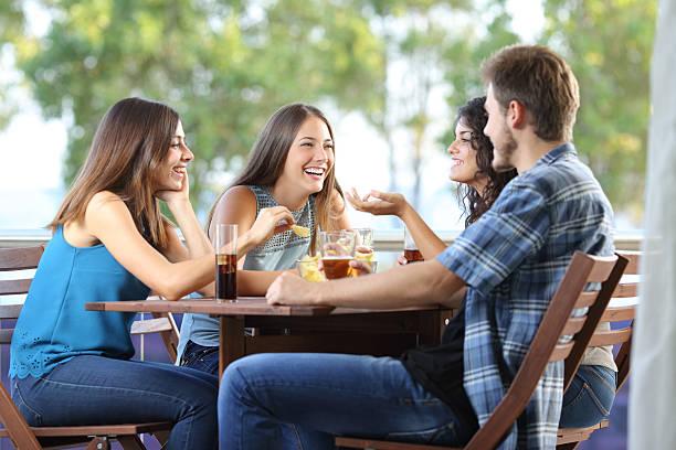 grupo de amigos hablando y bebiendo en su casa - couple lunch outdoors fotografías e imágenes de stock