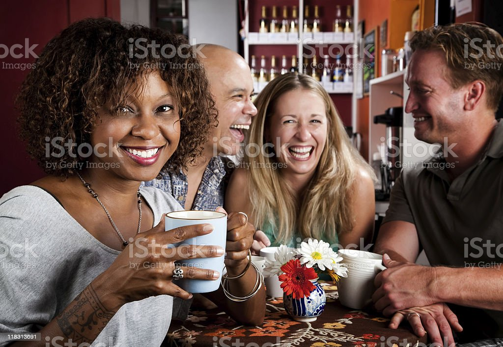 Group of friends talking over coffee in a cafe stock photo