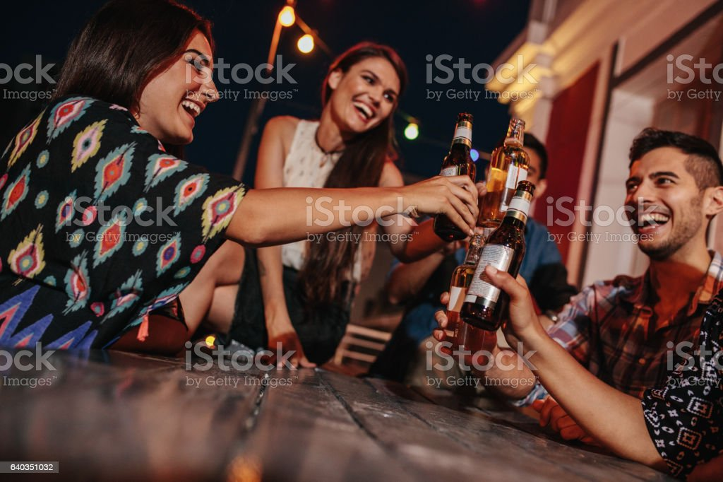 Group of friends toasting drinks at party in evening stock photo