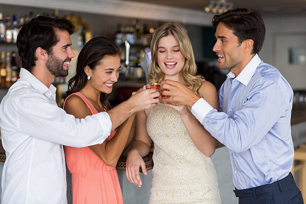 Group of friends toasting  glasses of tequila shot Group of friends toasting  glasses of tequila shot tequila shot stock pictures, royalty-free photos & images
