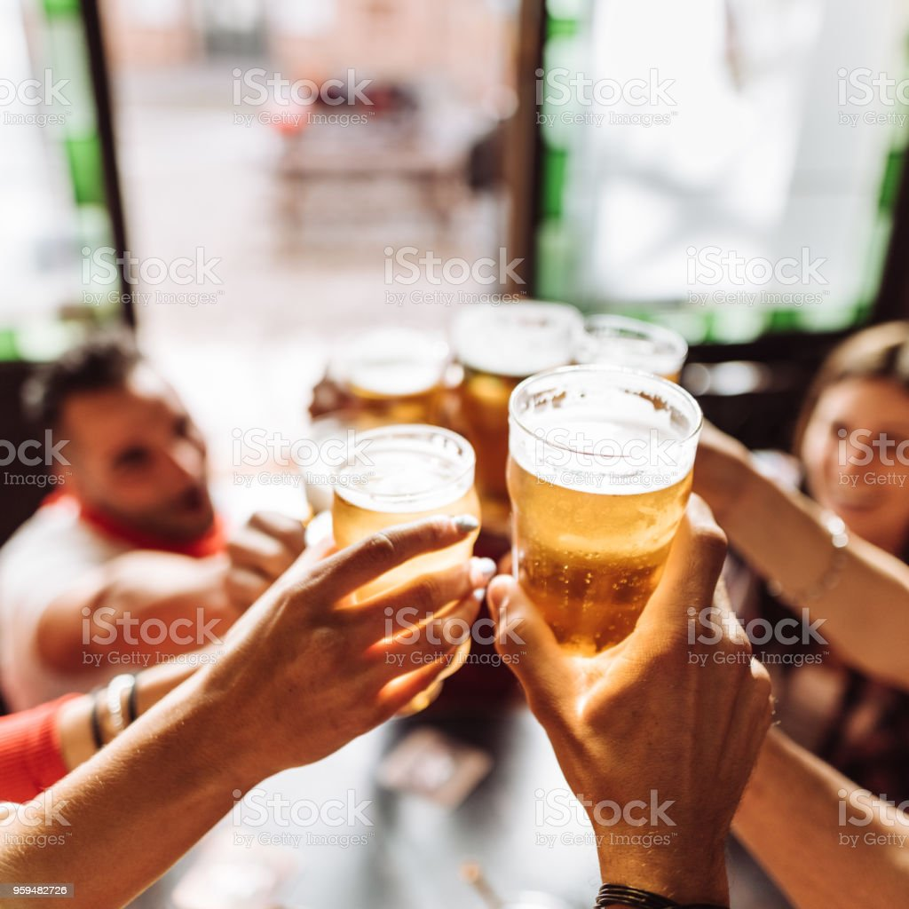 group of friends toasting the beer in a pub stock photo