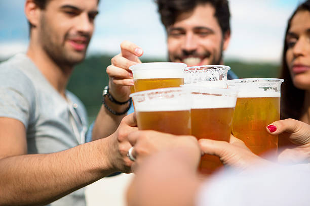 Group of friends toasting with beer in plastic glasses stock photo