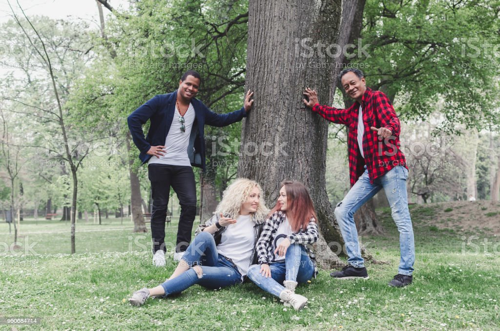 Group of friends together in a park having fun stock photo