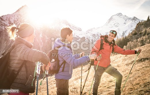 istock Group of friends trekking on french alps at sunset - Hikers with backpacks and sticks walking on mountain - Wanderlust travel concept with young people at excursion in wild nature - Focus on right guy 858650072
