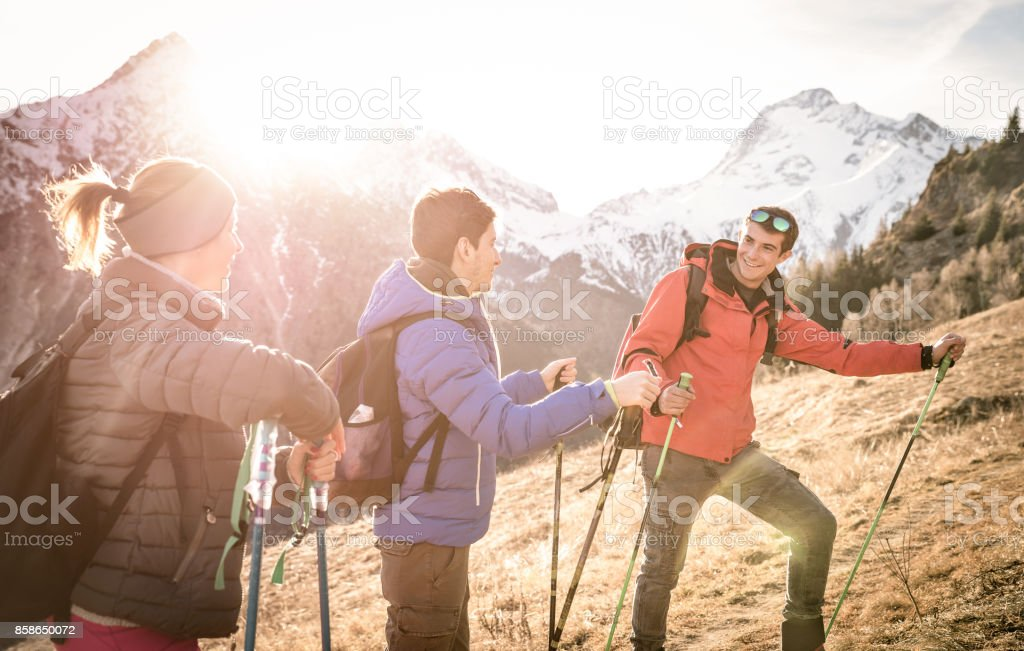 Group of friends trekking on french alps at sunset - Hikers with backpacks and sticks walking on mountain - Wanderlust travel concept with young people at excursion in wild nature - Focus on right guy stock photo