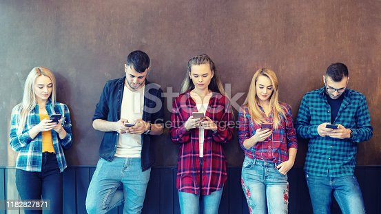 644191686 istock photo Group of friends using smartphone against wall at university college backyard break - young hipster people addicted by mobile smart phone - technology concept with online connected millennials 1182827871