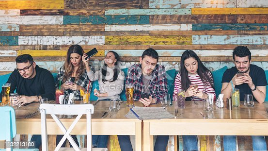 Group of friends using smartphone at rustic restaurant - Young hipster people addicted by mobile phone on social network community - Technology concept with always connected millennials