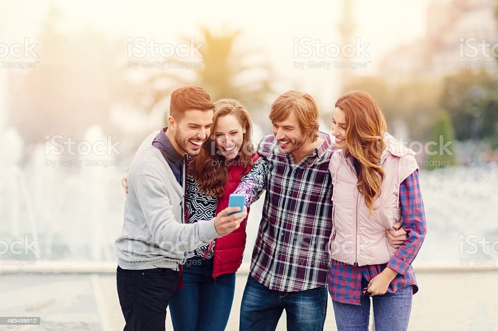 Group of friends using smartphone outside stock photo