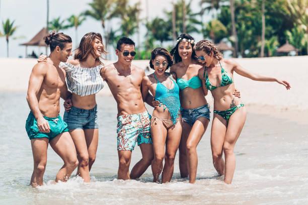 grupo de amigos que vadeia no oceano - com os pés na água - fotografias e filmes do acervo