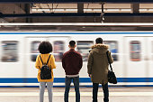 istock Group of friends waiting the train in the platform of subway station. 906647970