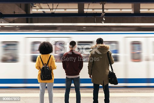 Group of friends waiting the train in the platform of subway station. Public transport concept.