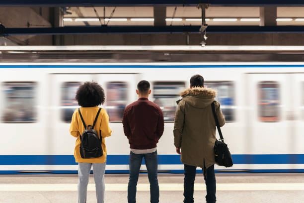 Group of friends waiting the train in the platform of subway station. stock photo