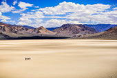 A group of friends making their way across the surface of the Racetrack Playa on a sunny day; mountains and white clouds in the background; Death Valley National Park, California