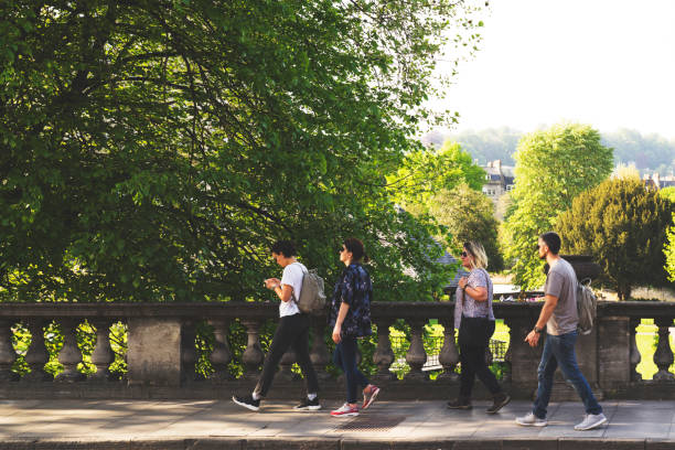 Group of friends walking in Bath city Group of friends walking in Bath city, looking for direction somerset england stock pictures, royalty-free photos & images