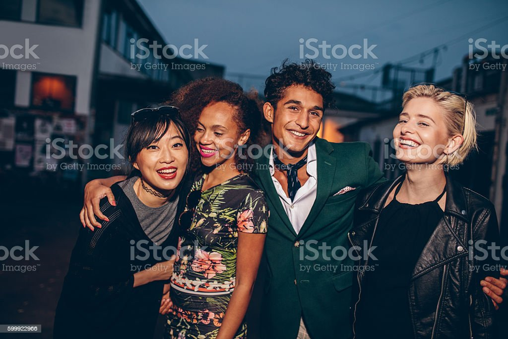Group of friends walking on city street together at night stock photo