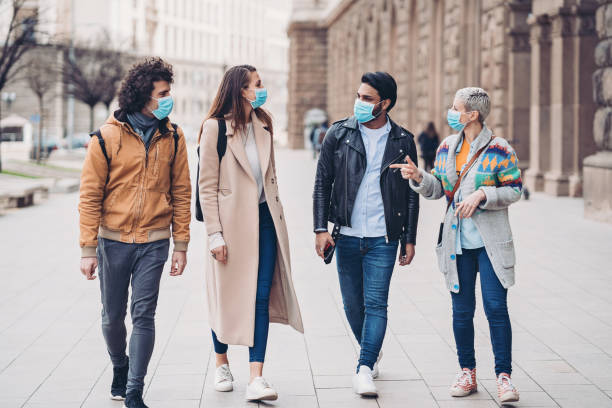 Group of friends walking together during virus epidemic stock photo