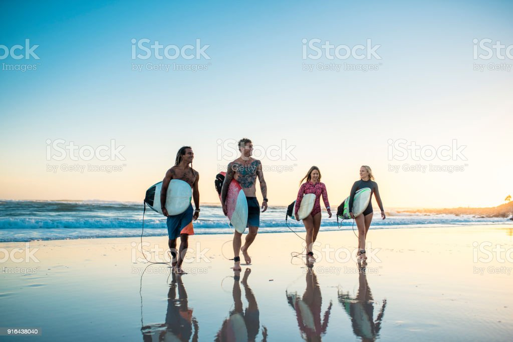 Group of friends walking with surfboards at the beach stock photo