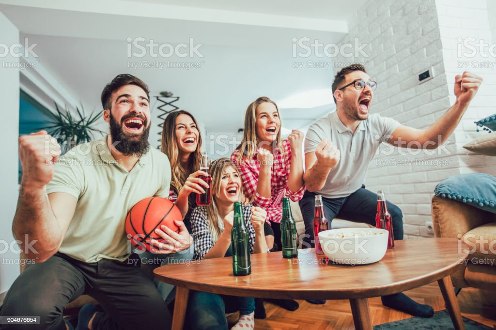 Group of friends watching a basketball game on tv stock photo