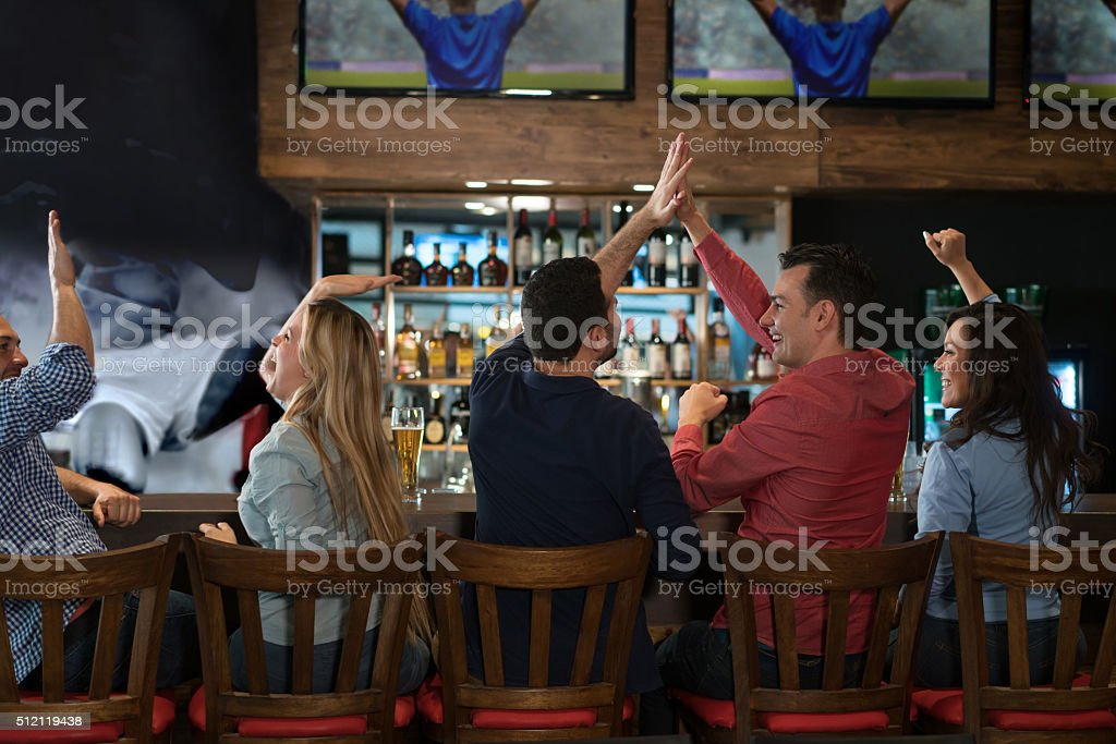 Group of friends watching a football game at the pub stock photo