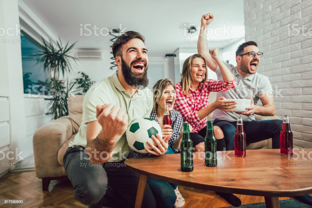 Group of friends watching a football match on tv stock photo