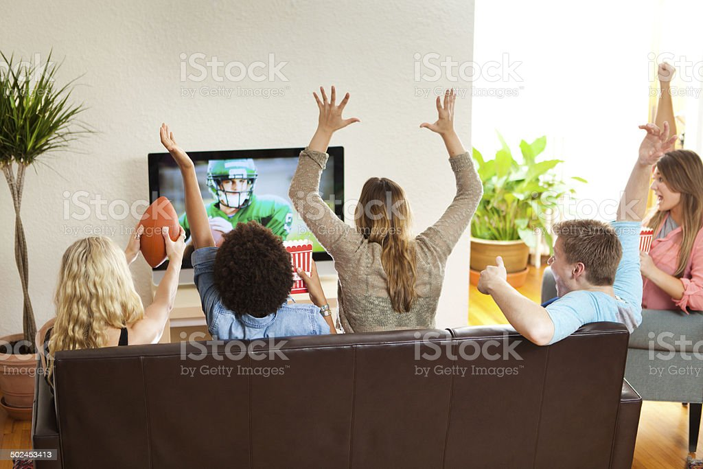 Group of Friends Watching and Cheering Football Game Together stock photo