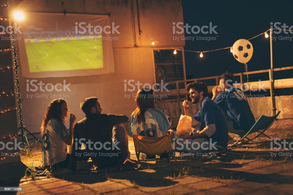 Grupo de amigos assistindo futebol em um telhado do edifício - foto de acervo