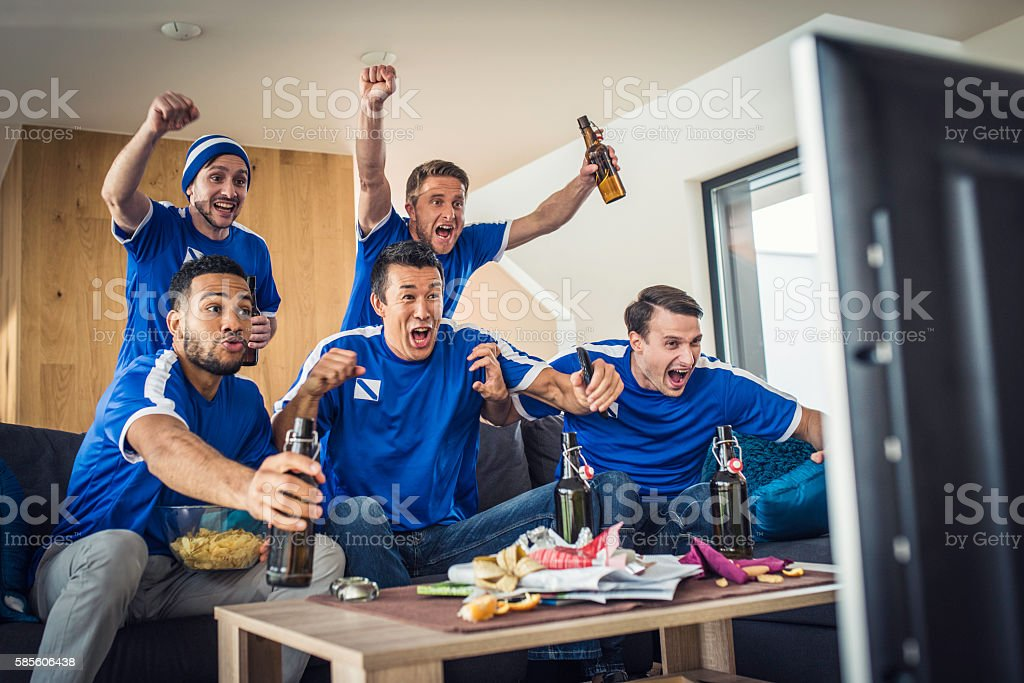 Group of friends watching game on TV stock photo