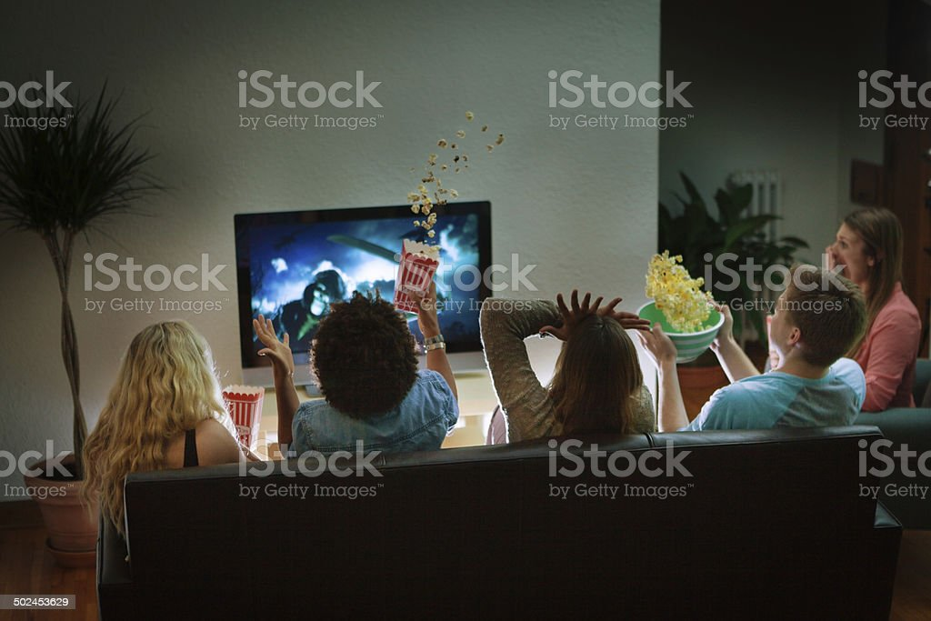 Group of Friends Watching Halloween Scary Movie Together at Home stock photo
