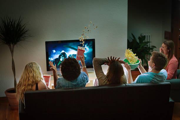 grupo de amigos a olhar para dia das bruxas assustador filme juntos em casa - tv e familia e ecrã imagens e fotografias de stock