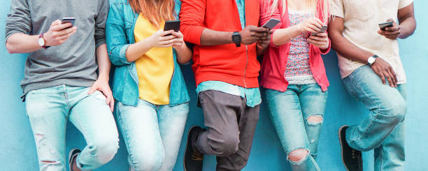 Group of friends watching smart mobile phones - Teenagers addiction to new technology trends - Concept of youth, tech, social and friendship - Main focus on center hands stock photo