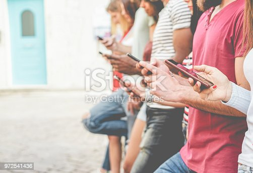 istock Group of friends watching smart mobile phones - Teenagers addiction to new technology trends - Concept of youth, tech, social and friendship - Focus on close-up phone 972541436