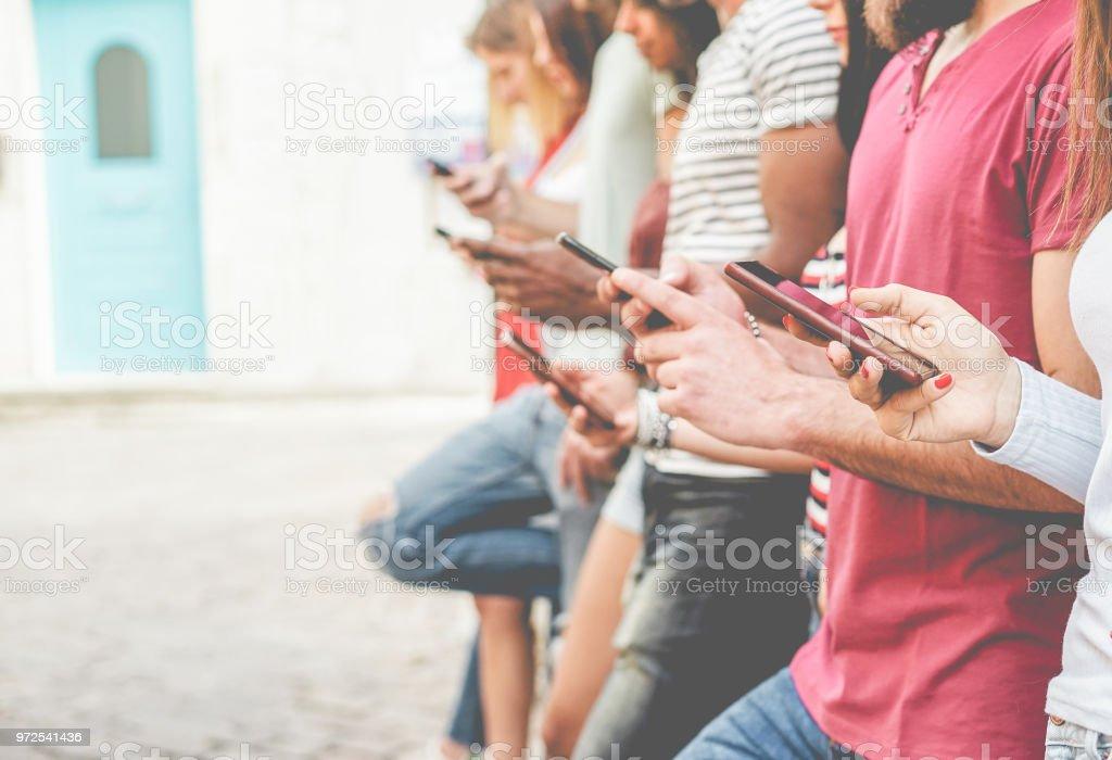 Grupo de amigos assistindo celulares inteligentes - vício de adolescentes, a nova tecnologia tendências - conceito de juventude, tecnologia, social e de amizade - foco telefone close-up - foto de acervo