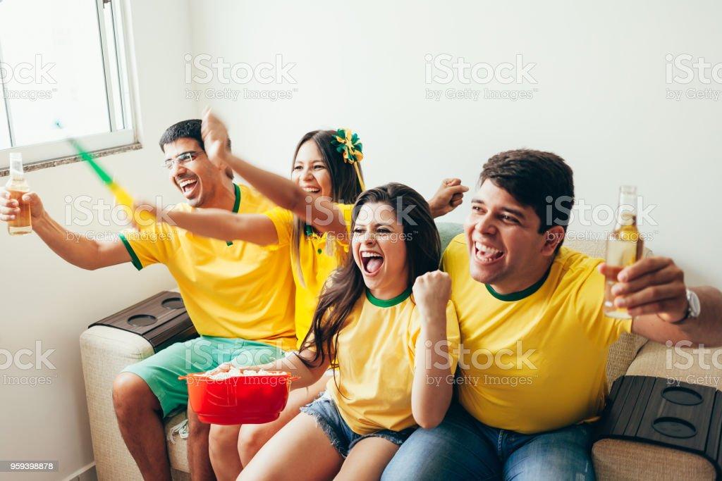 Grupo de amigos assistindo jogo de futebol na televisão, comemorando gol e gritando - foto de acervo
