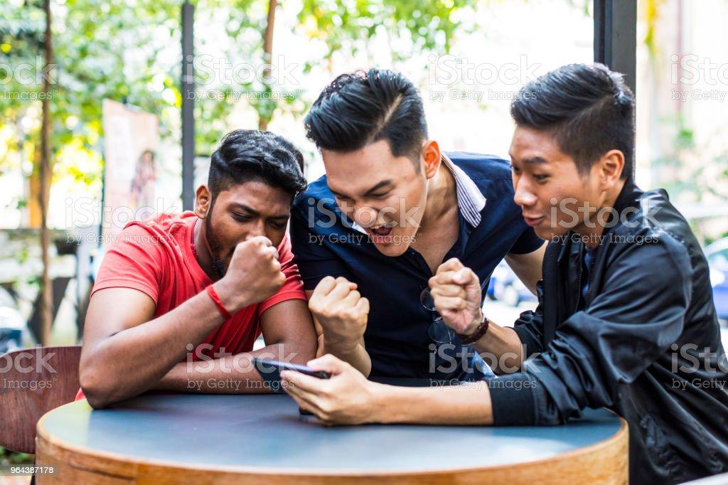 Grupo de amigos assistindo o seu jogo favorito em um telefone celular - Foto de stock de 20 Anos royalty-free