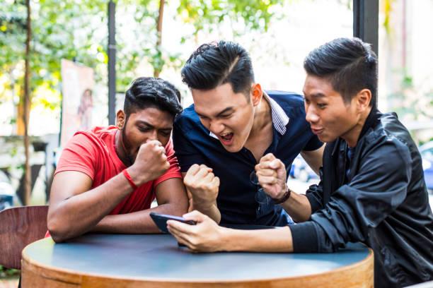 Groupe d'amis regarder leur match préféré sur un téléphone mobile - Photo