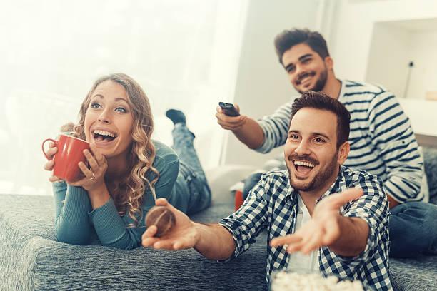 Groupe d'amis en regardant la télévision à la maison - Photo