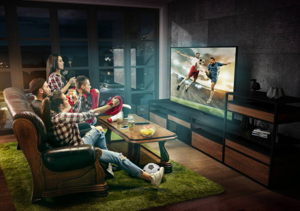 Group of friends watching TV, football match, sport together stock photo