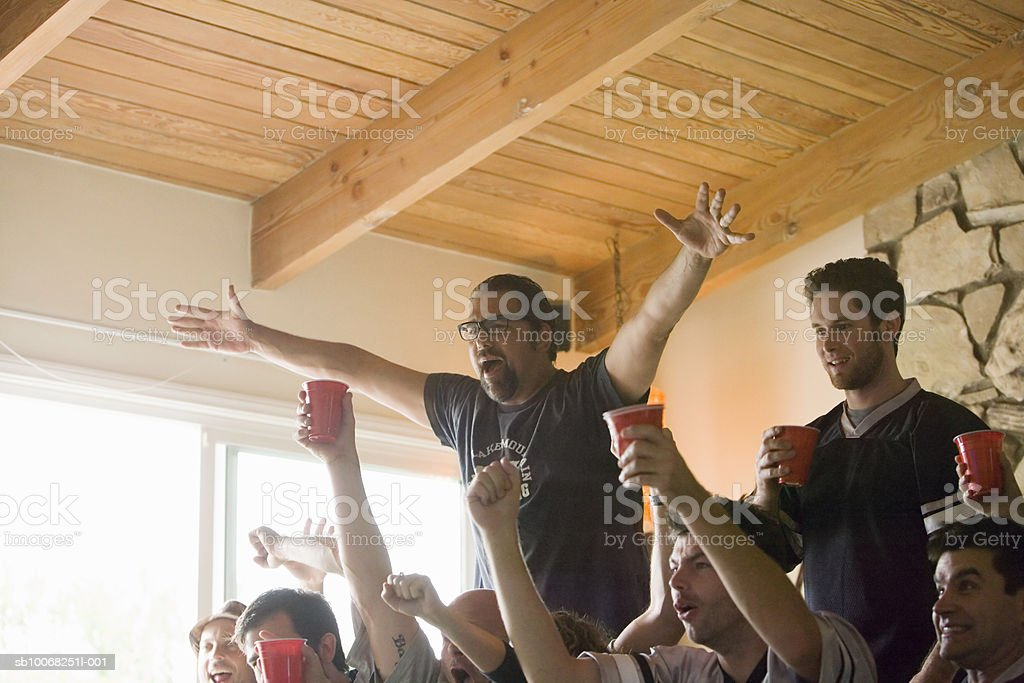 Group of friends watching tv, gesturing and yelling royalty-free stock photo