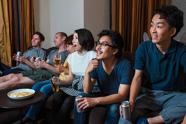 group of friends watching tv together - japanische themenpartys stock-fotos und bilder