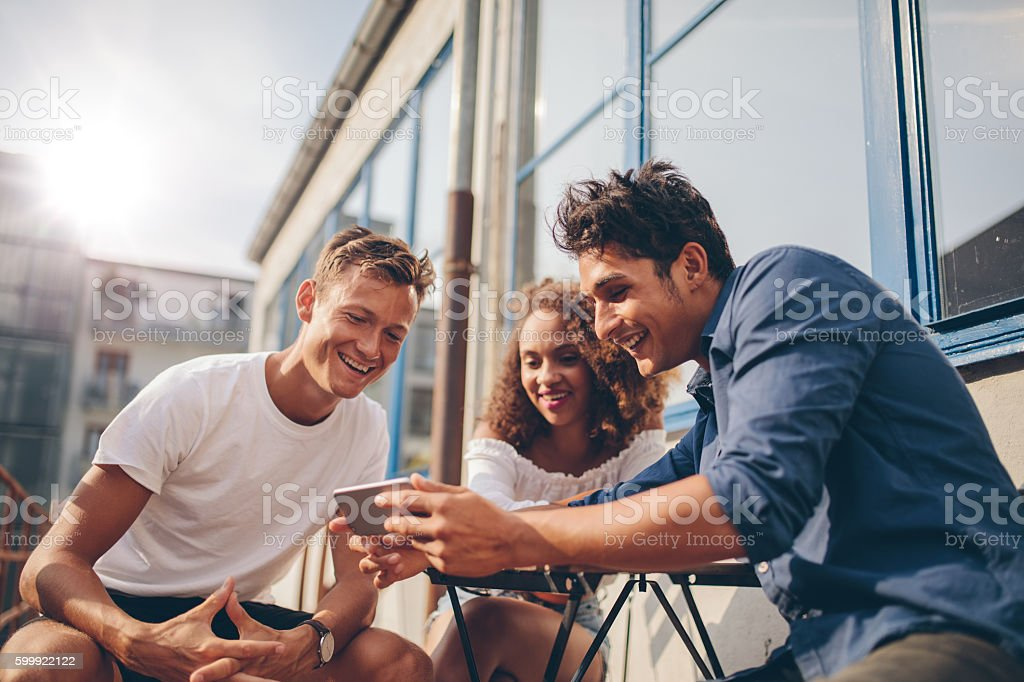 Group of friends watching video on smartphone stock photo