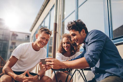 Group Of Friends Watching Video On Smartphone Foto de stock y más banco de imágenes de Adulto