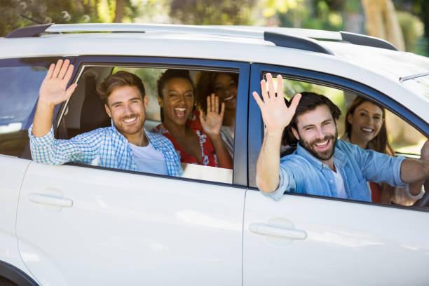 groupe d'amis agitant les mains de voiture - homme faire coucou voiture photos et images de collection