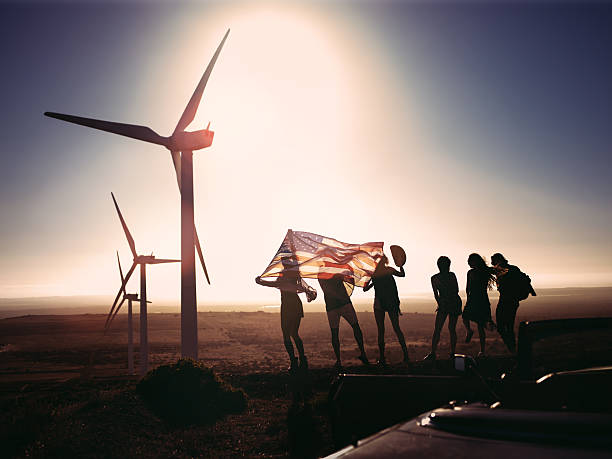 Group of friends with American flag visiting a wind park stock photo