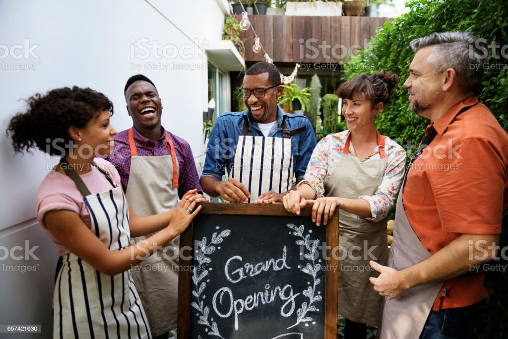 Group of friends with grand opening board together stock photo