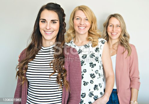 A Group of friends woman portrait close to a white wall