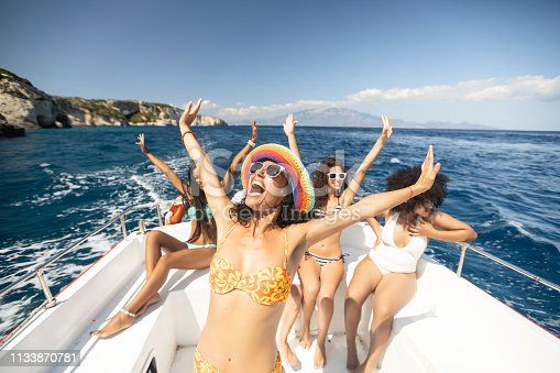Group of friends yachting and having fun, enjoying vacations.