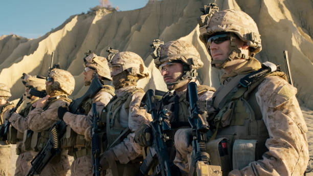 Group of Fully Equipped Soldiers Standing in a Line in the Desert. stock photo