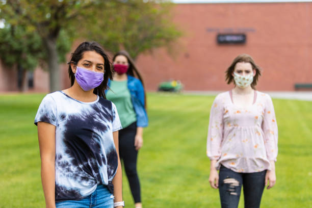 group of generation z multi-ethnic female friends wearing face masks and social distancing - social distancing stock pictures, royalty-free photos & images