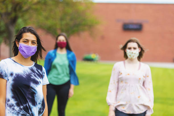Group of Generation Z Multi-Ethnic Female Friends Wearing Face Masks and Social Distancing on School Campus stock photo